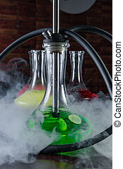 Stylish oriental shisha concept. Smoking hookah on dark table, in clouds of smoke and light. Glass hookah flask with green liquid and cucumber slices. Colored flasks on smoky blurred black background.