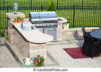 Stylish outdoor kitchen on a brick patio - High angle view...