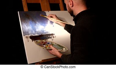 Stylish painter goes on drawing a new painting with oil paints holding the palette in his hand on easel, black background, back light