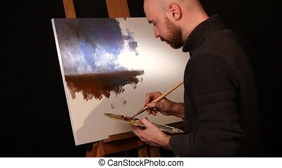 Stylish painter goes on drawing a new painting with oil paints holding the palette in his hand on easel, black background, back light, slow motion