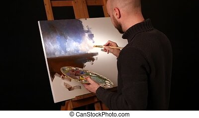 Stylish painter goes on drawing a new painting with sky and ground by oil paints on easel holding the palette in his hand, black background, back light, slow motion