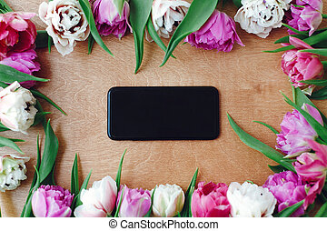 Stylish phone with blank screen flat lay in beautiful double peony tulips frame on wooden table. Happy mother's day. International women's day. Hello Spring. Greeting card mockup