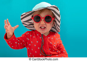 Stylish playful kid in sunglasses and striped hat