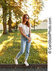 Stylish pretty girl in high-waisted jeans, white T-shirt and sneakers in a park on a background of trees at sunset.