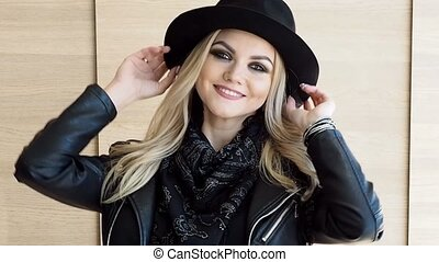 Stylish pretty woman in hat smiling and sending kiss -...