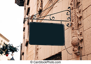 Stylish rectangular blank sign in a wrought-iron frame hangs on the stone wall of an ancient building