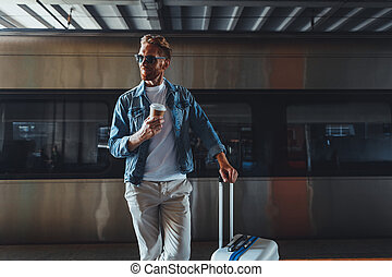 Stylish red haired man in sunglasses waiting for train