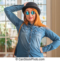 Stylish redhead woman wearing bowler hat and sunglasses confuse and wonder about question. Uncertain with doubt, thinking with hand on head. Pensive concept.