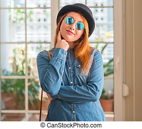 Stylish redhead woman wearing bowler hat and sunglasses with hand on chin thinking about question, pensive expression. Smiling with thoughtful face. Doubt concept.