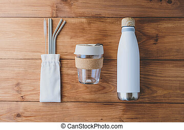 Stylish reusable eco friendly items on wooden background.