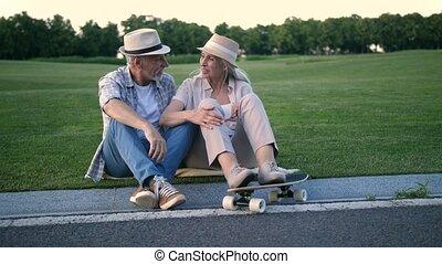Stylish senior couple sitting with a skateboard