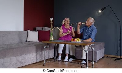 Happy stylish senior couple smoking hookah, eating fruits at home. Modern trendy elderly grandparents celebrating their anniversary relaxing having fun together enjoy care love tenderness. Slow motion