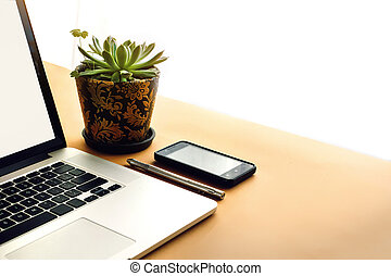 stylish silver laptop pen phone and succulent on wooden craft background, marketing work and freelance concept, flat lay