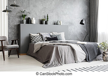 Bright bedroom interior in grey color with a big bed, an armchair and many lamps against textured wall. Pillows, linen and blankets on the bed. Real photo.