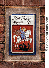 Stylish street sign with enameled paint of Saint George and dragon.