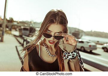Provocative good-looking girl taking off glasses and glancing