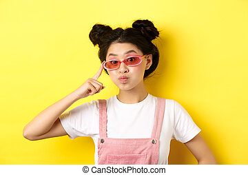 Stylish teen asian girl wearing sunglasses and pink overalls, standing on yellow background