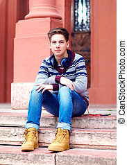 stylish teenage boy with headphones, sitting on stairs