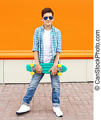 Stylish teenager boy wearing a shirt, sunglasses and skateboard in city