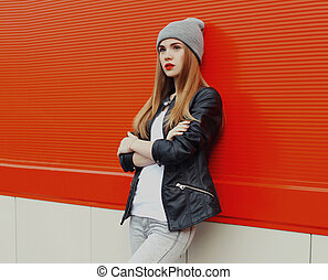 Stylish teenager girl posing in the city on a red wall background