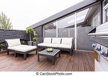 Stylish terrace with garden furniture - Side view of grill...
