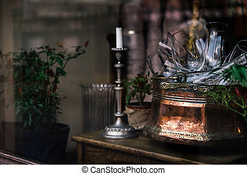 stylish vintage bowl with glasses and candle in a window, celebration decoration for holidays in the city