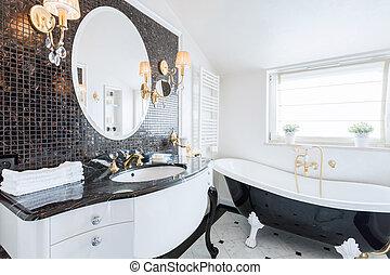 Stylish washroom with big black and white bathtub