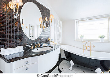 Stylish washroom with big black and white bathtub