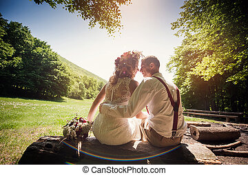 stylish wedding couple sitting on a bench in the park