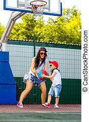 Stylish woman and little boy playing basketball