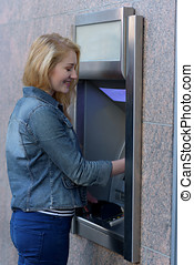 Stylish woman drawing money at an outdoor bank ATM