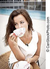 Stylish woman drinking tea