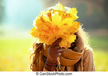 stylish woman holding yellow leaves in front of face