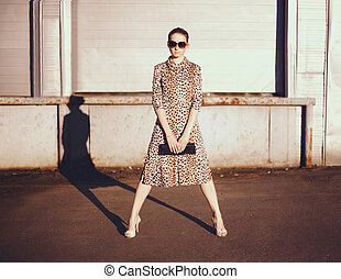Stylish woman in a leopard dress, glasses and bag in the...