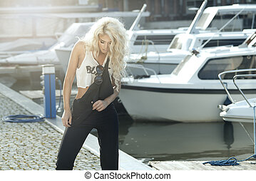 Stylish woman in dungarees standing on marina