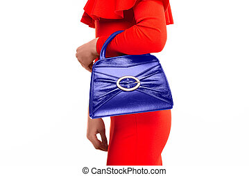 Stylish woman in red dress with small blue handbag