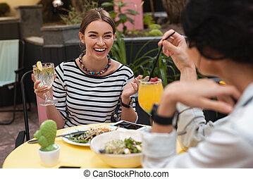 Stylish woman laughing while having lunch with best friend