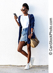 Stylish woman listening to music on mobile phone