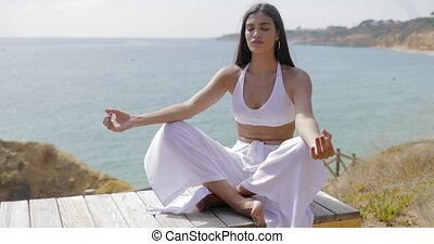 Stylish woman meditating on nature