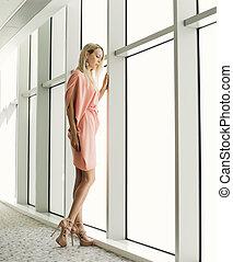stylish woman near window in the office building