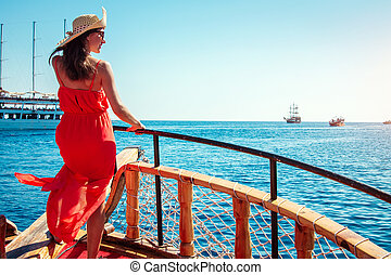 Stylish woman on a wooden yacht