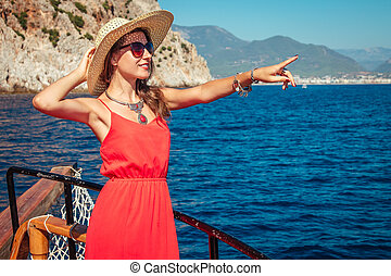 Stylish woman on a wooden yacht