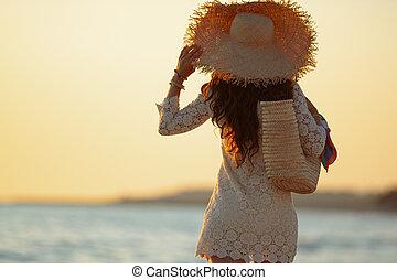 stylish woman on beach at sunset walking