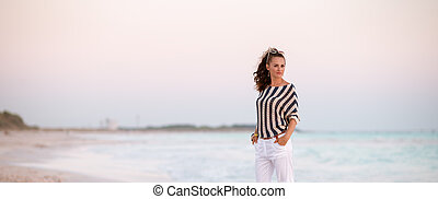 stylish woman on beach in evening