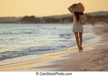 stylish woman on seacoast at sunset walking