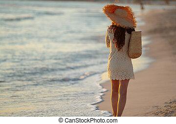 stylish woman on seashore at sunset walking