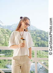 Stylish woman resting with cup of coffee on balcony in front of mountains.