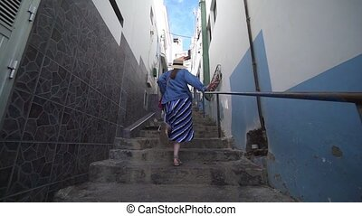 Stylish woman runs up the stairs in a very narrow street in the old Spanish city. A tourist walks around the city of El Pris, Tenerife, Spain