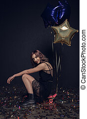 stylish woman sitting on skateboard with balloons during party