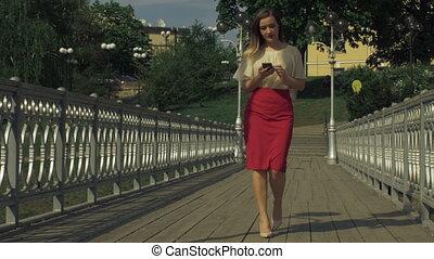Stylish woman using smart phone app on city bridge